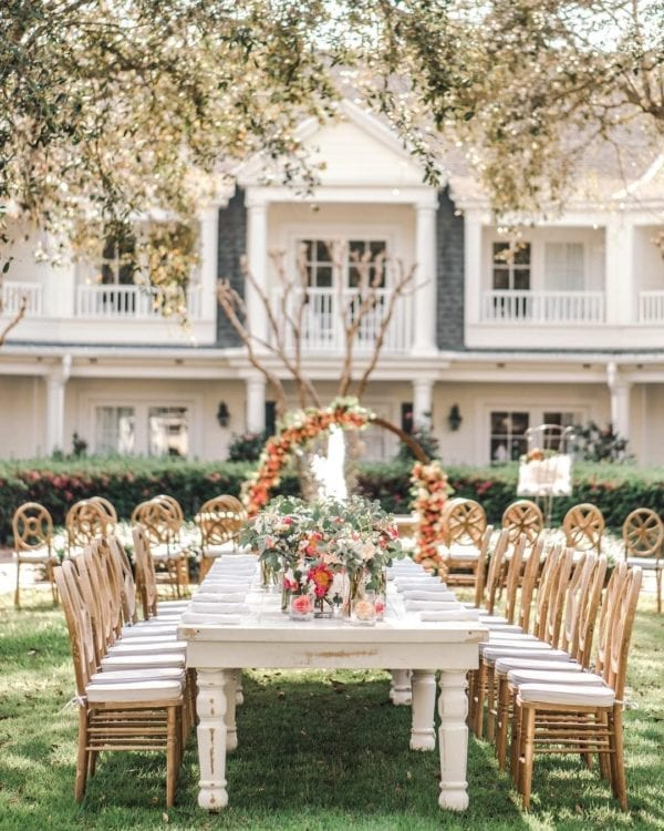 dreamy rustic wedding with white washed farm table and natural wood chairs