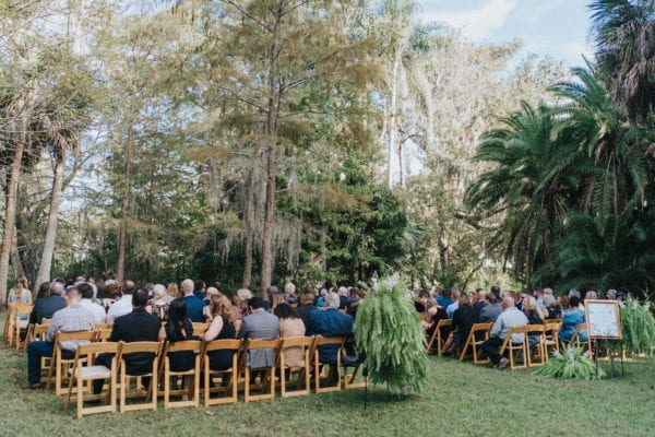 natural wood folding chairs at an outdoor wedding ceremony