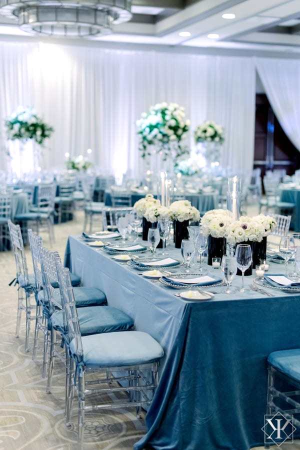 silver beaded charger plates, and kings table, and clear chiavari chairs at a wedding reception at the alfond inn in winter park florida