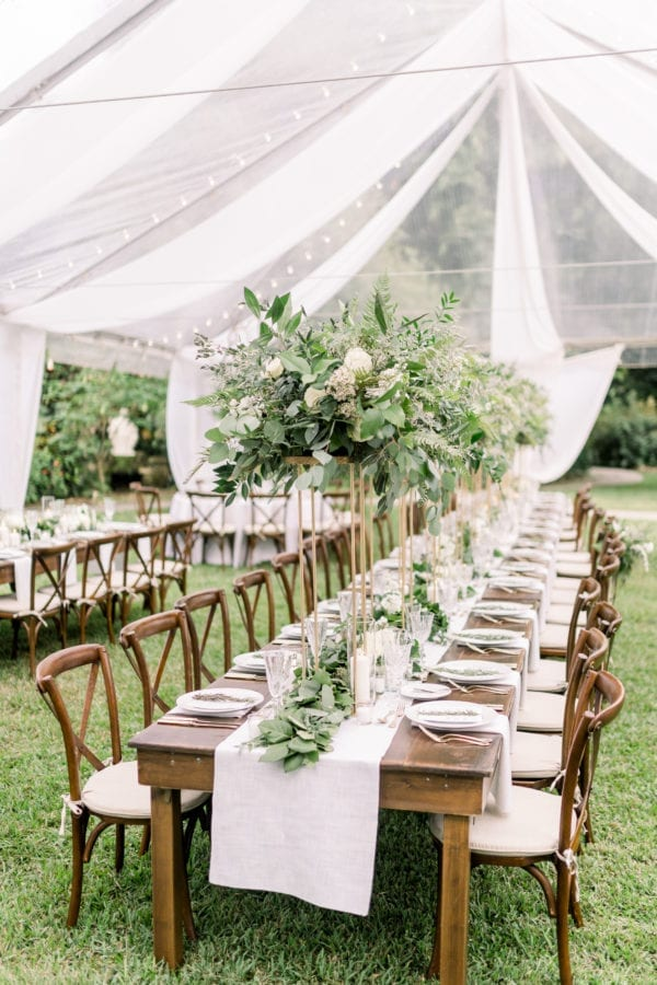 french country chairs and farm tables under a clear tent at capen house in winter park florida